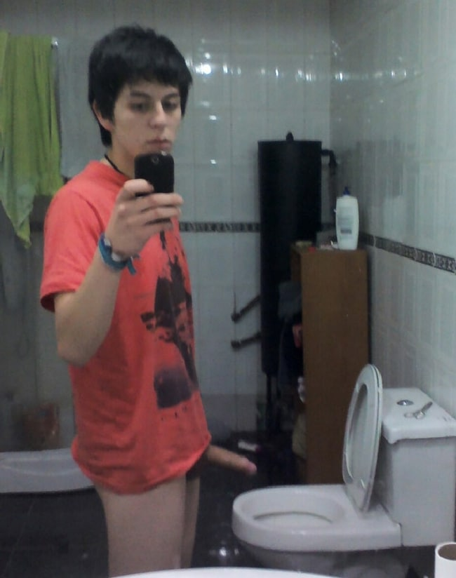horny teen boy in a red tshirt taking a picture of his hard penis